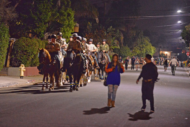 Mounted deputies from the Santa Barbara County Sheriff's Department patrol a relatively deserted Del Playa Drive in Isla Vista on Saturday night. Officials said the historically raucous Halloween celebration was subdued this year.