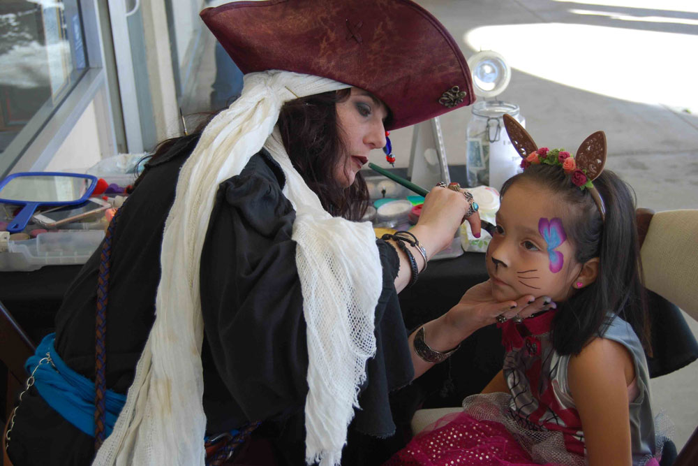 "Tea in Tiaras owner Karrinne Galle paints a butterfly and cat whiskers on Melanie Alonzo, 4, at the ""Halloween Extravaganza"" in Goleta."