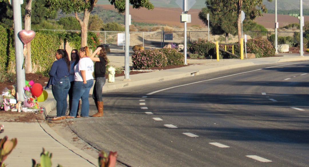 Mourners gather around a makeshift memorial on East Donovan Road in Santa Maria on Saturday. A Righetti High School senior driving a car full of teenagers died of her injuries after the vehicle hit a light pole Friday night.