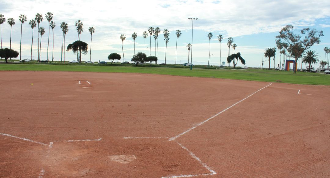 The ball diamond at Santa Barbara's Cabrillo Ball Field is expected to get an outfied fence under city Parks & Recreation Department plans to improve the site at the intersection of Cabrillo Boulevard, Milpas Street and Calle Puerto Vallarta. Also under consideration are possible basketball courts, an adult fitness area, a dog park or a skate plaza in the west corner, near the Chromatic Gate art installation in the distance to the right.