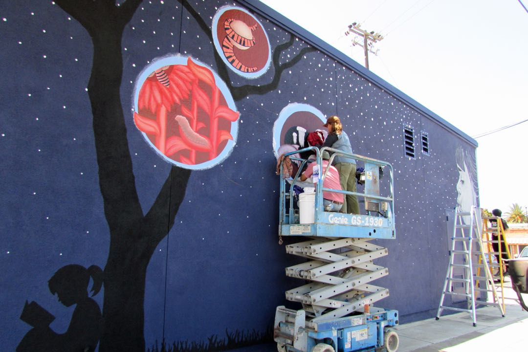 With the help of a scissor lift and ladders, artists and students work on the Santa Maria Valley Discovery Museum mural.