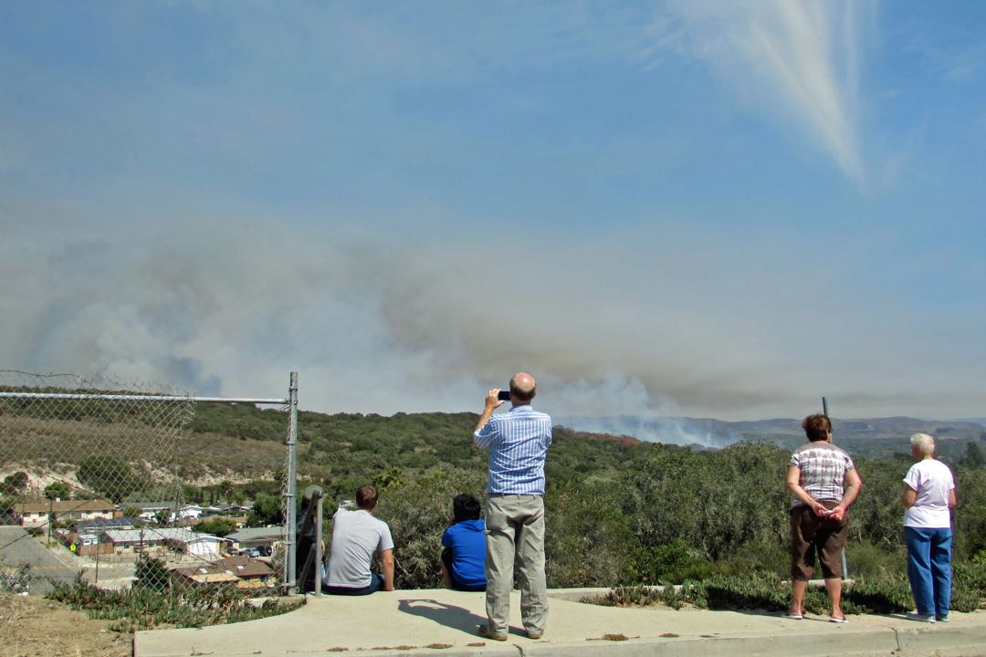 Mission Hills residents watch the Burton Mesa fire burn in a nearby canyon June 29 before a flare-up sent black smoke billowing into the sky.