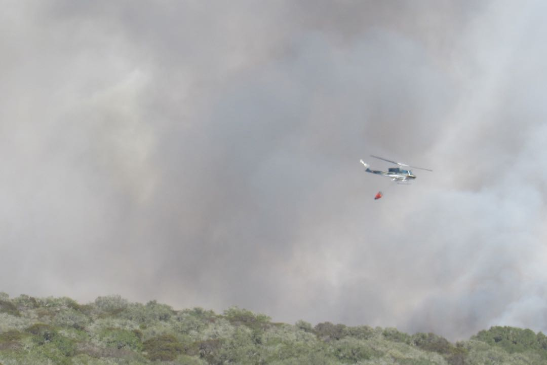 A helicopter is dwarfed by billowing smoke above the Burton Mesa fire burning near Lompoc on June 29.