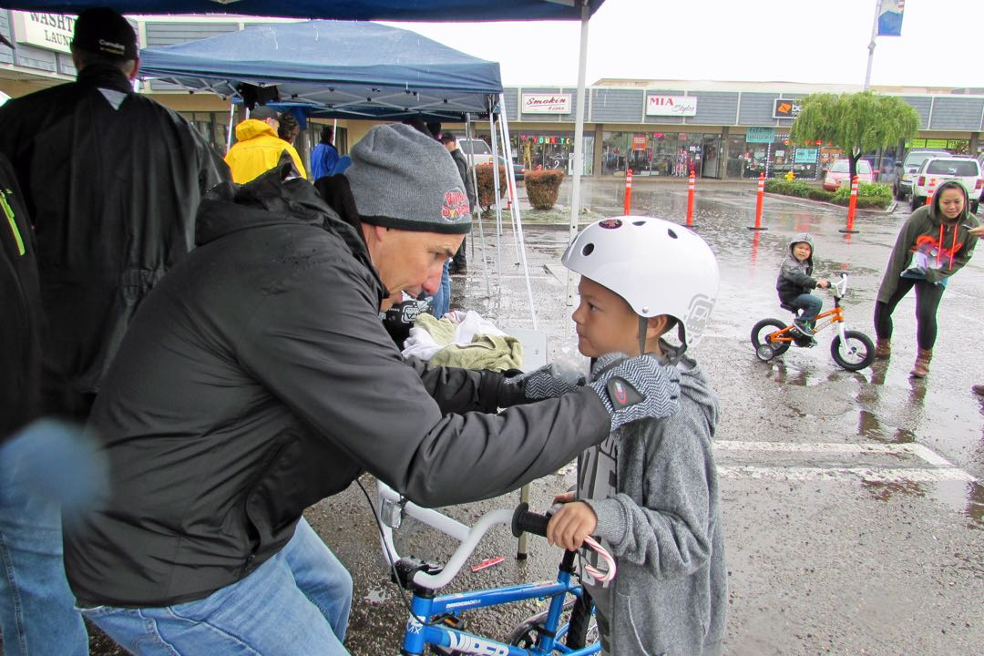 Village Dirtbag member Randy Baumgardner adjusts a bicycle helmet on Ethan Chang, 8, while his brother, Brayden, rides his new bike in the background.