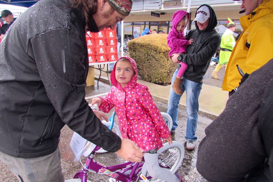 A Village Dirtbag member adjusts a girl's new bicycle Saturday.