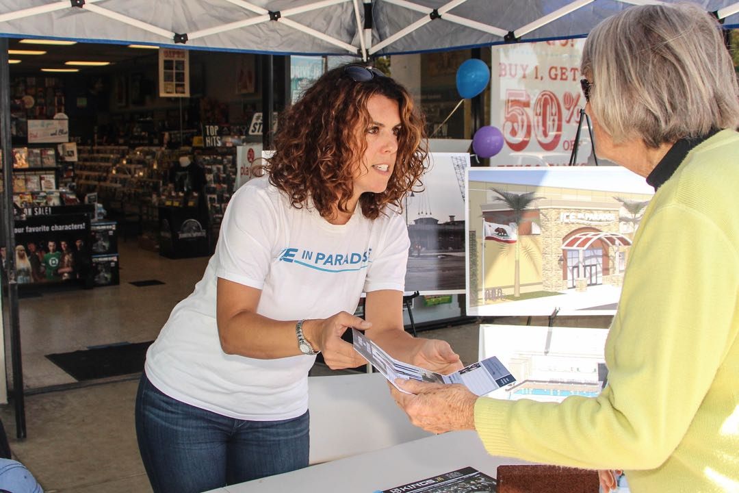Jennifer Ono of Ice in Paradise shares a brochure with a visitor to the group's booth at the Fourth Annual Caring & Sharing festival at the Calle Real Center in Goleta.