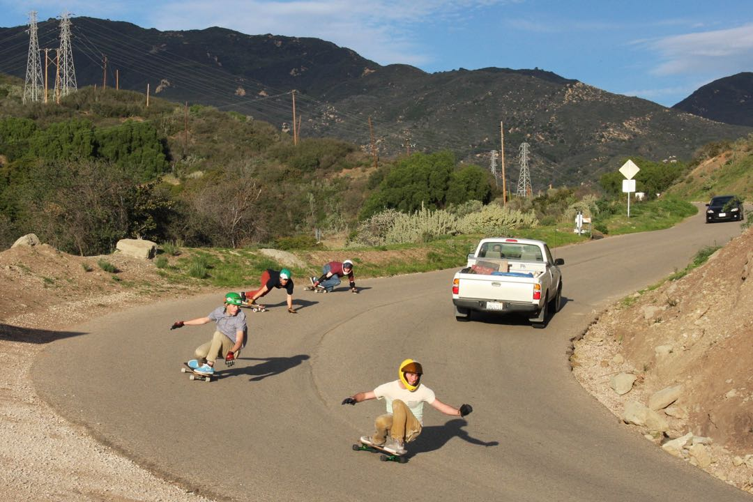 Skateboarders race past a pickup truck in the mountains above Santa Barbara.