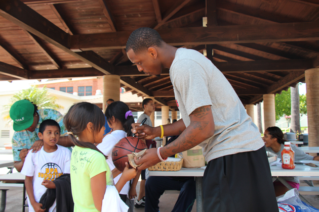 James Nunnally signs a basketball ball for a camp participant.