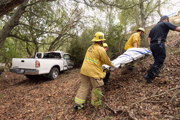 Santa Barbara County firefighters use a Stokes basket and rope system to transport a female patient from the crash site up to the roadway.