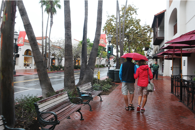 Pedestrians walk down Santa Barbara's State Street sheltered from the drizzle Monday afternoon.