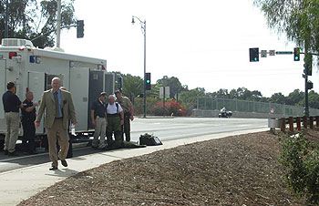 Police bomb squad officers prepare to probe and destroy a suspicious bag left behind by the suspect after his arrest on the bridge in the background.