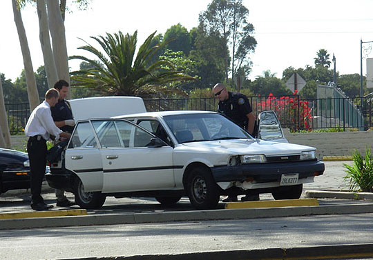 Santa Barbara police detectives search a suspicious vehicle in the parking lot of La Cumbre Plaza, near the scene of a standoff with an alleged gunman on the La Cumbre Road overpass in the background. The man apprehended in the incident hung an American flag and an Obama-Biden yard sign on the bridge, which remain faintly visible on the fence.
