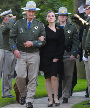 California Highway Patrol Capt. Jeff Sgobba walks Patricia Martinez to her limo after Wednesday's memorial service for her husband, Jarrod, who died last week in a traffic accident.