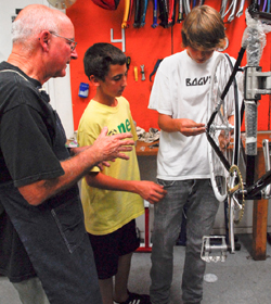 Volunteer Wilson Hubbel helps Alec Larson and Luke Ming work on a bicycle at a Bici Centro workstation.