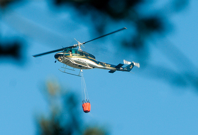 A Santa Barbara County sheriff's helicopter moves above the trees for a water drop on Tuesday afternoon.