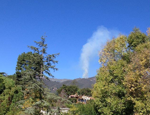 Smoke rises from a fire in Cold Springs Canyon in a view from Parra Grande Lane in Montecito.