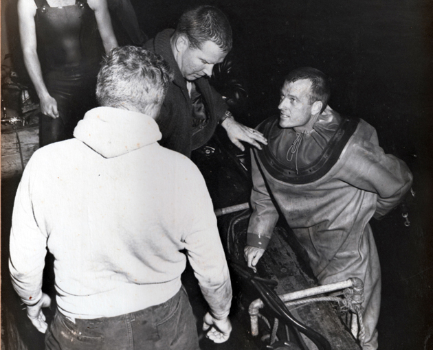 <p>Dan Wilson on the diving ladder aboard the vessel Rio Janeiro after completion of his 400-foot, record-setting oxy-helium dive on Nov. 3, 1962. Tenders Jim Houtz and Jerry Ruse assist.</p>