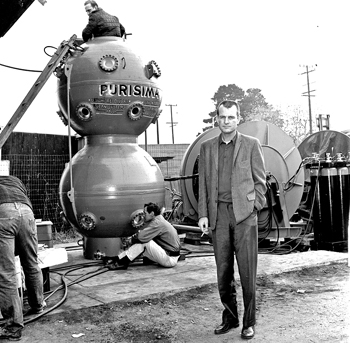 Dan Wilson with the 1,000-foot Purisima diving bell he designed in 1963 at his Santa Barbara abalone shop on Gutierrez Street. Whitey Stefens (top of bell) prepares the bell interior for testing. (Bev Morgan photo)
