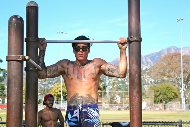 Luiz Munoz performs a muscle-up during a Santa Barbara Bar Life workout session.