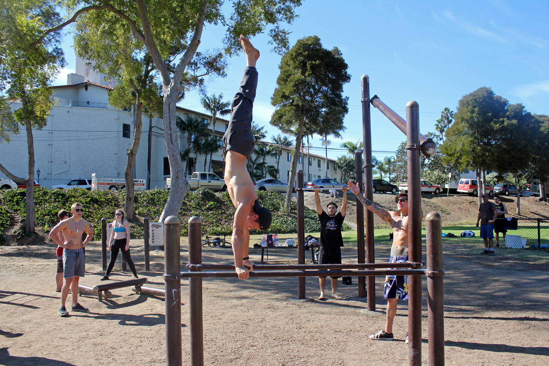 Drew Janssen performs a bar stand as other members of Santa Barbara Bar Life cheer him on.