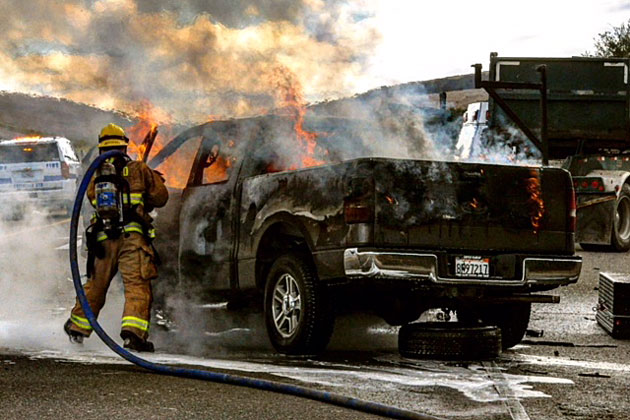 A firefighters douses flames Wednesday after a pickup truck caught fire following an accident on southbound Highway 10 near Orcutt.