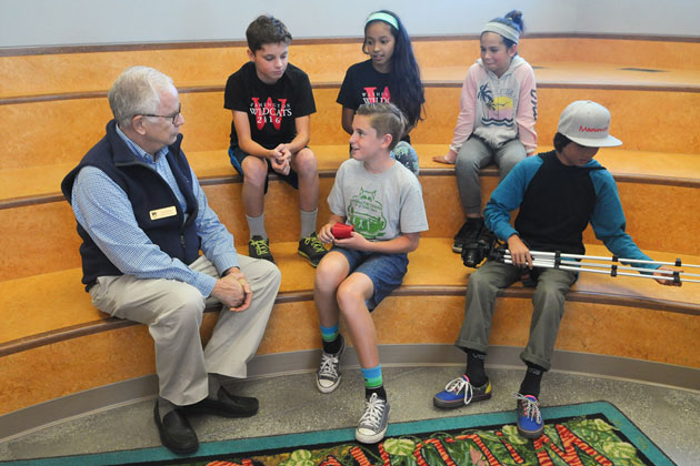 Ed Heron, president of the Santa Barbara school board, sits with students in the reading area of the new library at Washington Elementary School.