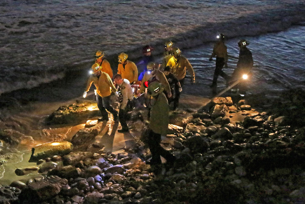 Santa Barbara County firefighters carry a man to a waiting ambulance after he fell some 30 feet from an apartment balcony to the beach below Isla Vista. The victim was taken to Goleta Valley Community Hospital with minor injuries.