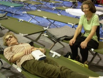 Evacuees Geneva Cheves and her mother, Roxanne, find refuge at San Marcos High School, where the gymnasium had been converted into an American Red Cross-Santa Barbara County Chapter emergency shelter lined with 200 cots.