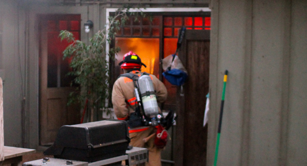 <p>A Montecito firefighter battles the flames of a home fire Friday on Tabor Lane.</p>