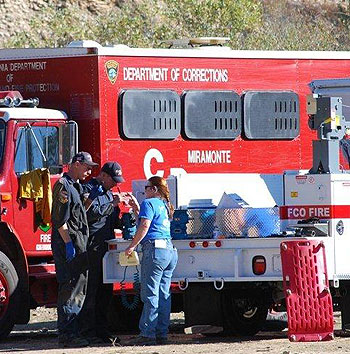 Fire crews do an equipment check at the Tea Fire's Live Oak staging area Sunday morning.