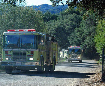 Fire trucks enter the Live Oak staging area after an all-nighter on the Tea Fire lines.