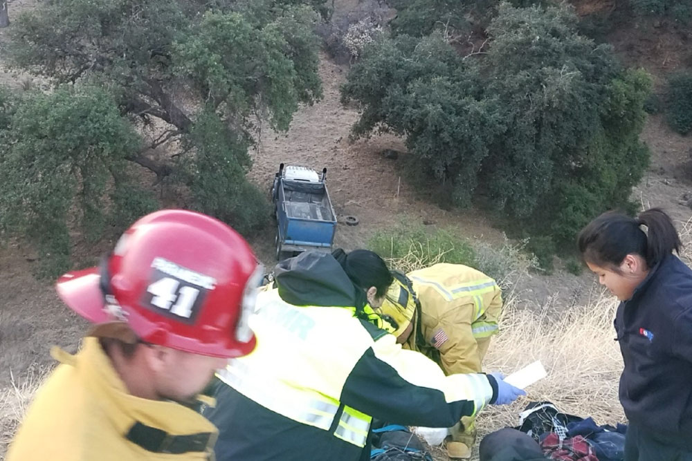 Emergency personnel carry an injured truck driver to a waiting ambulance Thursday after his big-rig plunged some 150 over the side of Highway 166 east of Santa Maria.
