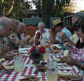 Larry Crandell. a longtime champion of Stow House, is the center of attention while holding court during a down-home barbecue.