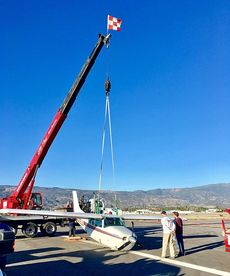 A crane is used to remove the damaged plane from the Santa Barbara Airport runway.