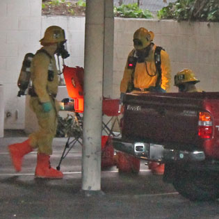 Hazmat Crews Gather In A Carport To Examine The Contents