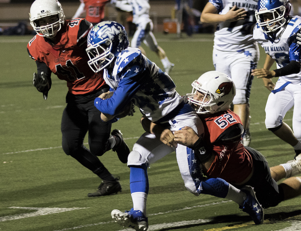 Bishop Diego's Chris Jablonka tackles San Marino running back Beau Hobbie for a short gain.