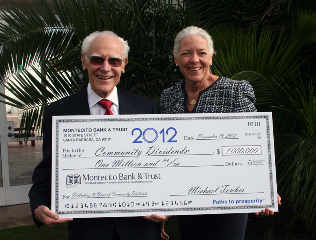 Montecito Bank & Trust founder and chairman Michael Towbes and CEO/President Janet Garufis hold up a $1 million Community Dividends check divided among 180 local nonprofits during Monday's 10th annual awards luncheon held at the Four Seasons Resort The Biltmore Santa Barbara. (Melissa Walker / Noozhawk photo)