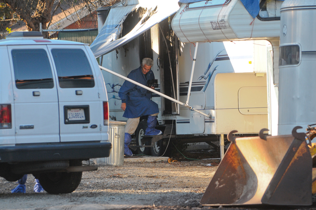 A sheriff's department investigator steps into the trailer where a dead man was found Thursday following a day-long standoff with law enforcement. The cause of death is unknown.
