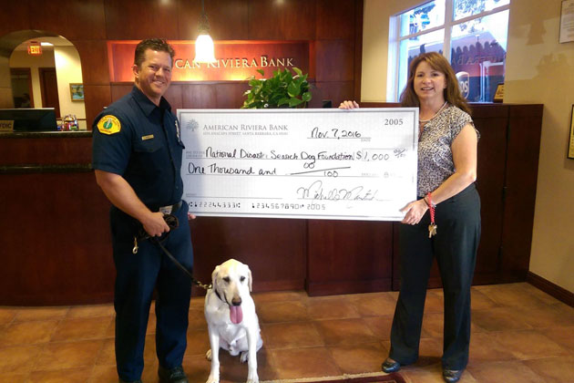 Eric Gray and Riley of Search Dog Foundation receive a $1,000 check from Laurra Mitchell of American Riviera Bank.