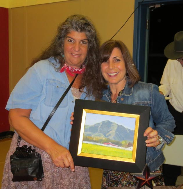 Volunteers Debbie Stevens and Geri Carty display a painting by local artist Arturo Tello.