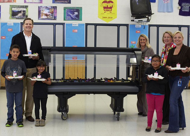 <p>Apio Inc. CEO Ron Midyett joins Adams students and staff in a lunchtime trip through one of the salad bars the company donated to 10 elementary schools in the Santa Maria-Bonita district.</p>