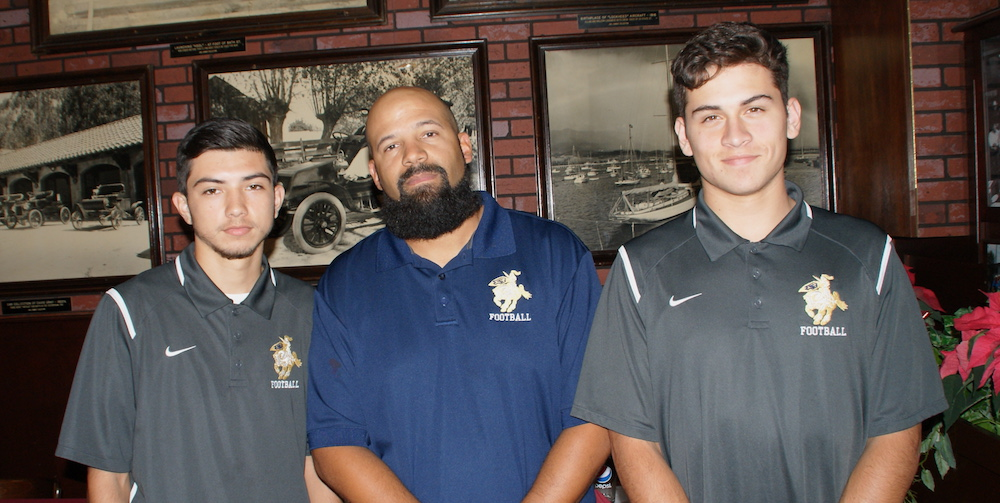 Dos Pueblos defensive coordinator Doug Caines is joined by standout members of the Chargers' secondary, senior cornerback Daniel Arzate, left, and senior free safety Michael Elbert.