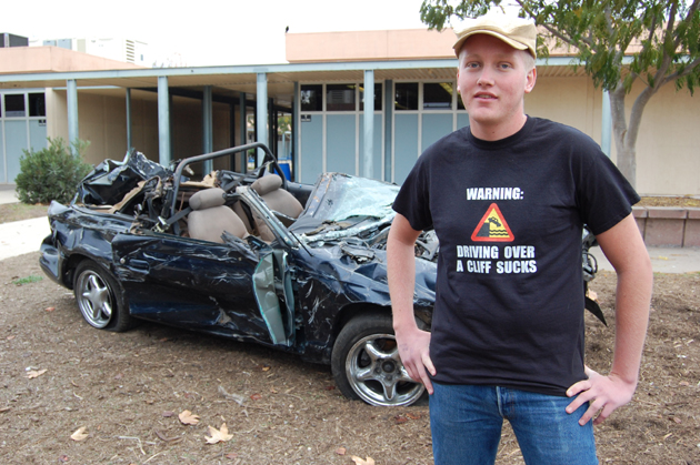 Dos Pueblos High School senior Thomas Dwelley, standing next to his smashed Mustang, talks on Wednesday about the crash that sent him careening 200 feet off the side of Gibraltar Road. The vehicle will be on display at the school for three days as a very visual reminder for students of what can go wrong. (Santa Barbara Unified School District photo)