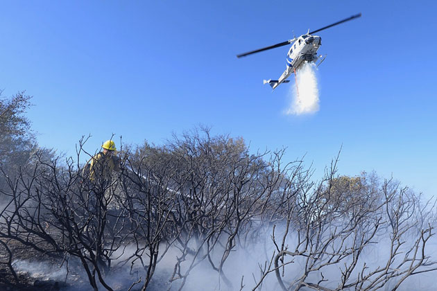 A Santa Barbara County helicopter makes a water drop on a fire that burned about an acre near the Winchester Gun Club along West Camino Cielo above Goleta.