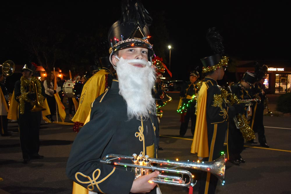 Sebastian Serniak, a ninth-grader in the Cabrillo High School Marching Band, sports a white beard and illuminated trumpet for the Lompoc Children's Christmas Season Parade on Friday night.