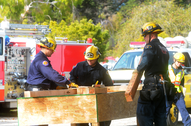 Fire crews work with lumber to build scaffolding as part of Tuesday's earthquake-preparedness drill. (Lara Cooper / Noozhawk photo)