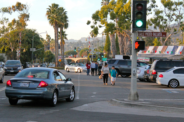 Pedestrians walk in the street in front of Tri-County Produce, one of the Lower Milpas Street locations Santa Barbara has identified as needing sidewalks.