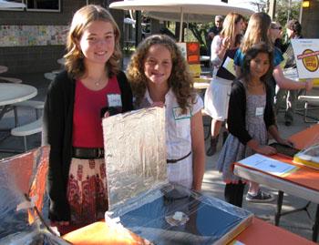 Hope District students Joslyn and Camryn cook marshmallows and chocolate in their solar ovens, made of pizza boxes, foil, plastic wrap and newspaper for insulation.