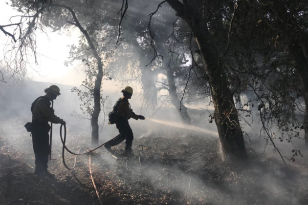 Fire crews hose down a vegetation fire burning near the intersection of Highway 101 and Highway 154 in Santa Barbara County Thursday afternoon.