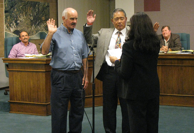 Newly elected Carpinteria City Councilmen Fred Shaw, left, and Wade Nomura take the oath of office Monday from City Clerk Fidela Garcia. (Giana Magnoli / Noozhawk photo)